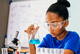 Indy STEAM Academy student wearing goggles with beaker and microscope