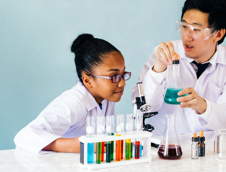 Indy STEAM Academy teacher and student in lab coats and goggles