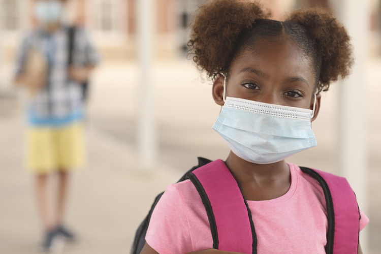 African American girl on school campus. She wears a mask for COVID-19, Coronavirus protection. Other student in background.