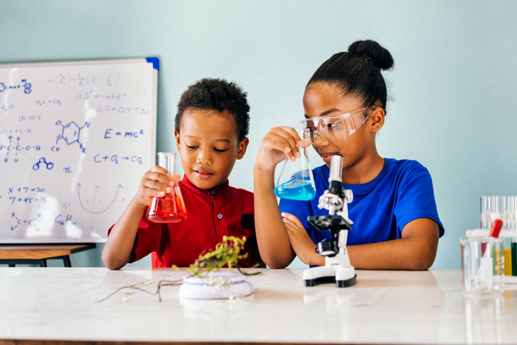 Boy and girl students at Indy STEAM Academy use beakers and microscope
