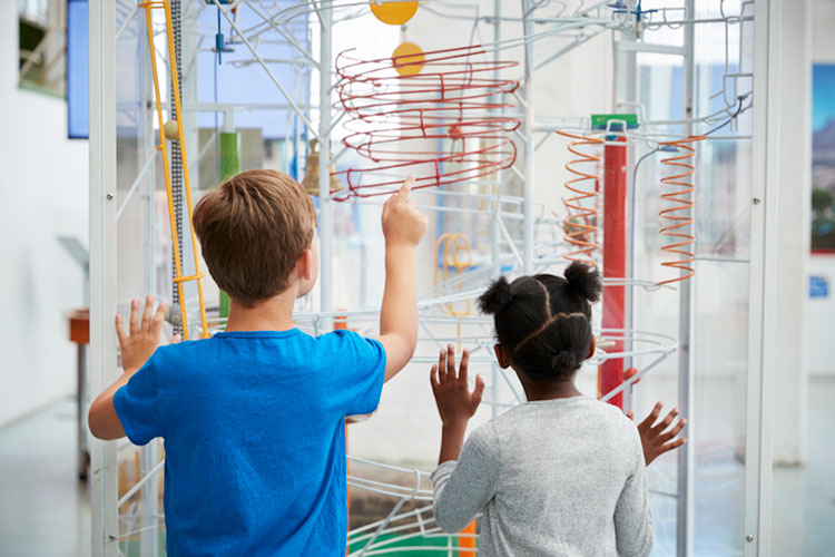 Boy and girl watch a ball maze with wonder