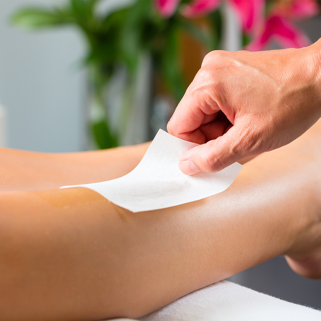 image of a leg being waxed by a professional at a day spa