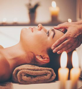 A woman at a spa with her head resting on her temples and the masseuse resting her hands on her temples.