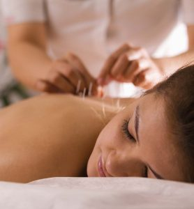 A woman lying on a massage table getting a massage.