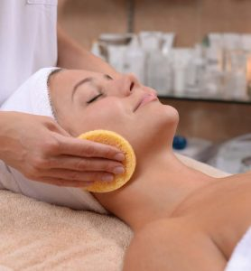 A woman getting a facial treatment at a spa.