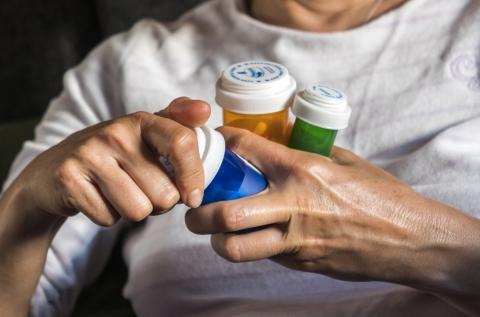 Woman holding three pill bottles.