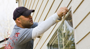 Worker Taping Off Home Exterior for Painting