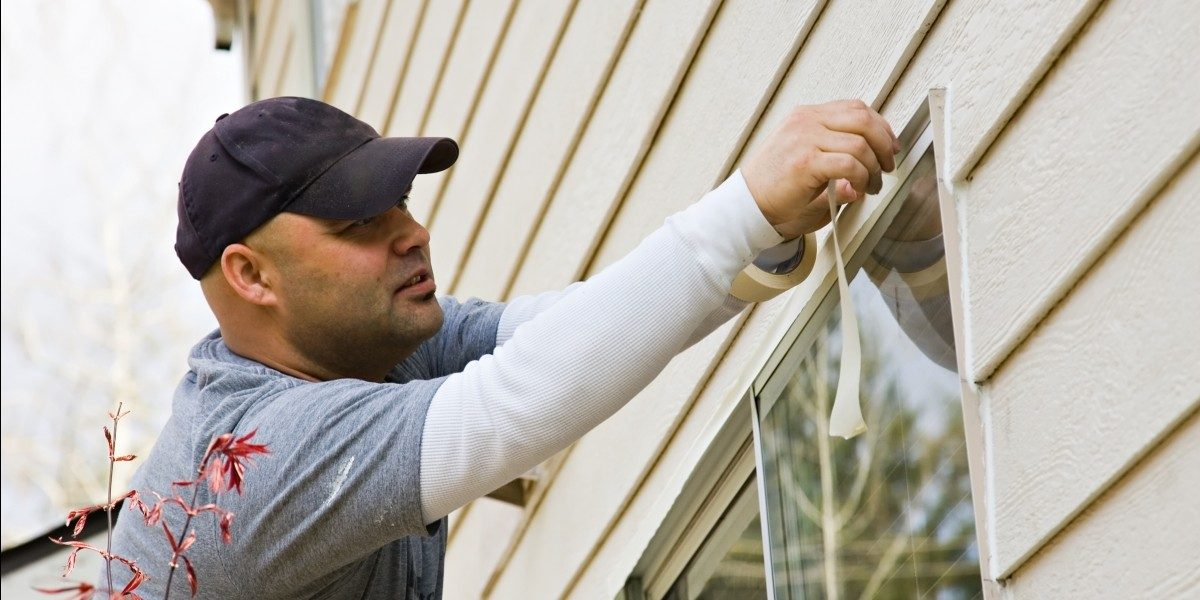 Man Taping Off Window for Painting