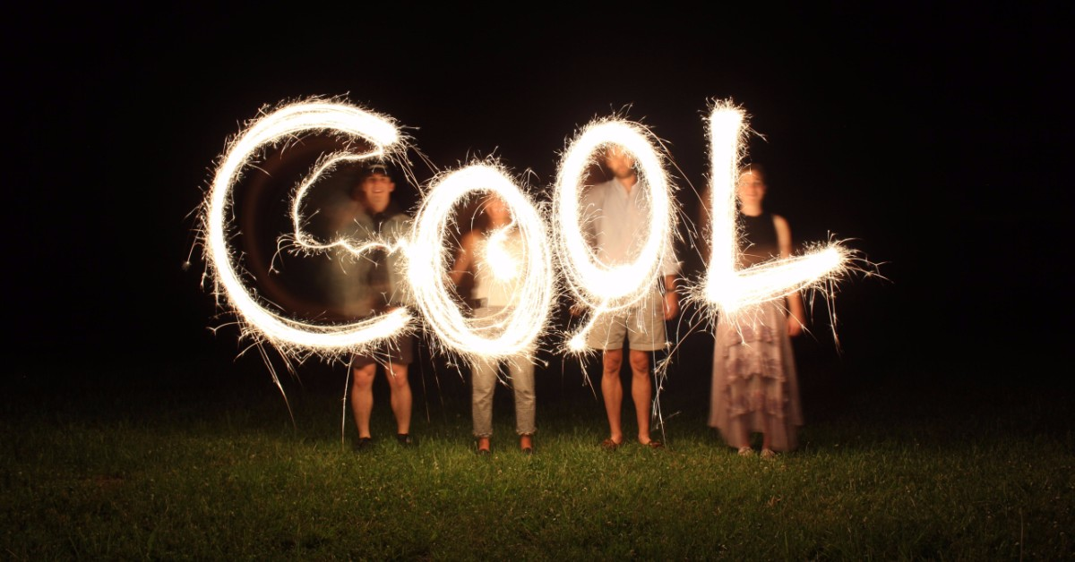The word COOL written with lights by four people standing on a green lawn at night.
