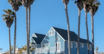 Image of a blue house surrounded by palm trees and a bright blue sky.