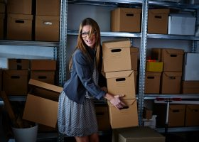 Woman Moving Boxes in Storage