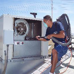 HVAC Tech Using Specialized Vacuum to Clean Commercial HVAC System