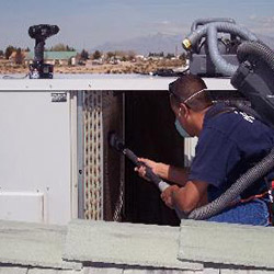 HVAC Tech Performing Cleaning on Commercial HVAC System