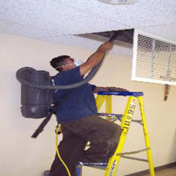 Specialist Cleaning Commercial Vents With Backpack Vacuum