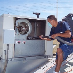 Specialist Cleaning a Commercial AC Unit