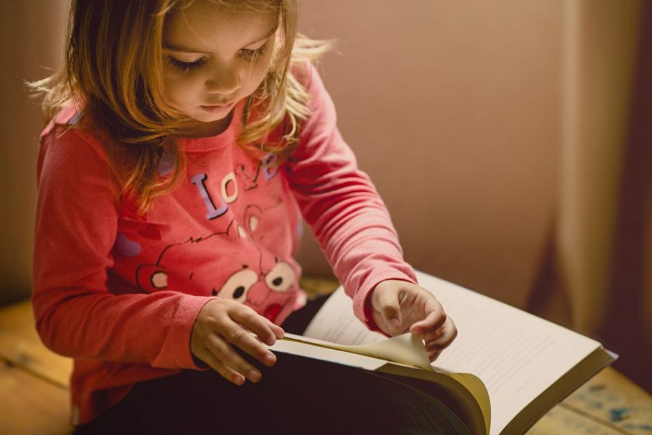A young girl wearing a pink shirt reads a book.