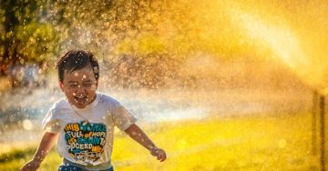 A small toddler smiles as he runs through the sprinklers in a yard on a hot summer's day. Photo by MI PHAM on Unsplash.