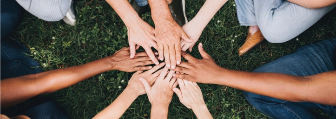 people-stacking-hands-together-in-the-park-picture