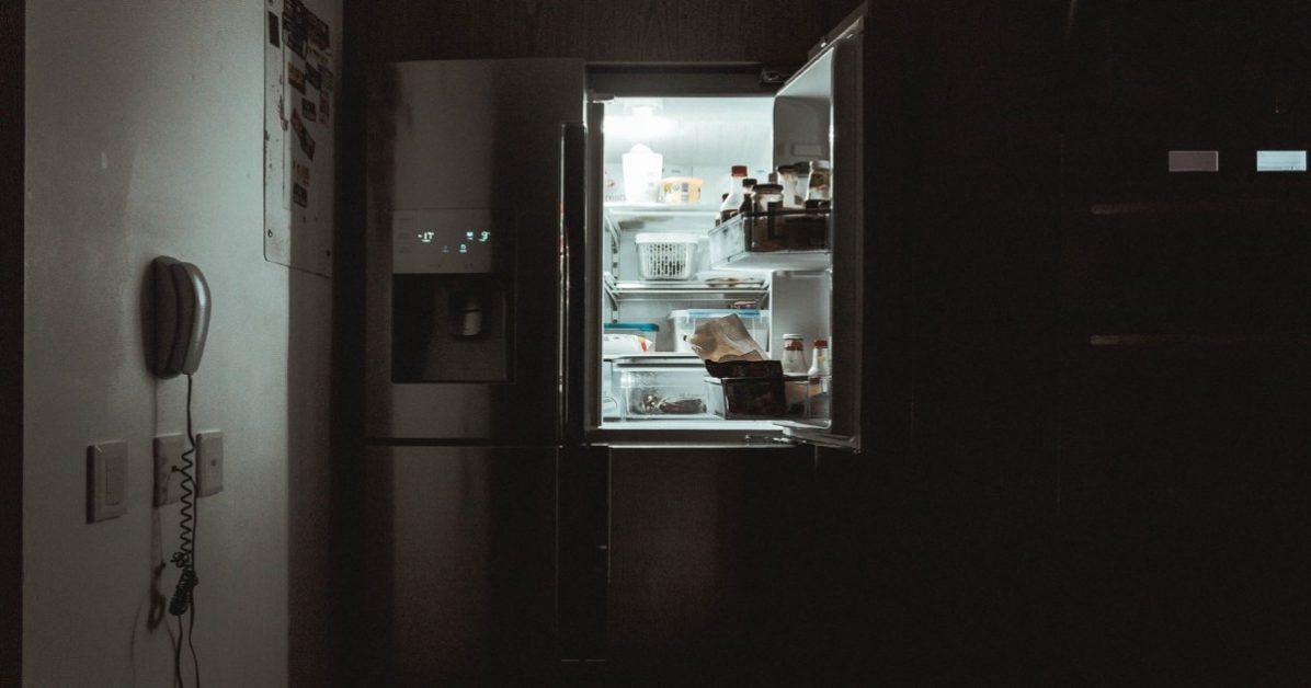 An open refrigerator lighting a dark kitchen