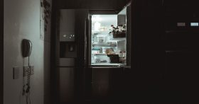 An open refrigerator lighting a dark kitchen