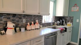 Kitchen with white cabinets, white counters, and stone backsplash - J&J Quality Construction