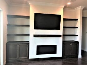 White fireplace with black shelving and t.v. - J&J Quality Contstruction