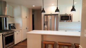 White kitchen with stainless steel fridge and black hanging lights - J&J Construction