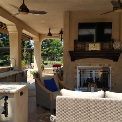 Wicker chairs sitting around a TV as part of an outdoor remodel