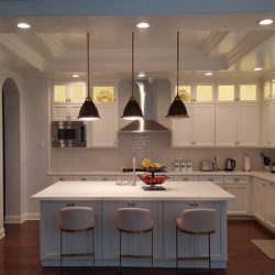 Kitchen renovation featuring white cabinetry and dark hardwood floors
