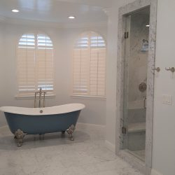 White bathroom remodeling with marble shower and custom blue and white tub
