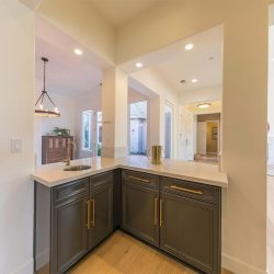 Home renovation with dark grey custom cabinets and a granite countertop featuring a small sink