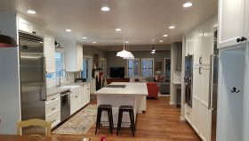 White kitchen island, stainless steel appliances, and white cabinetry in a Fresno kitchen renovation
