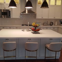 White kitchen island with white custom cabinetry