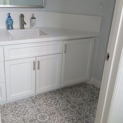 White bathroom with patterned tile floor and white cabinets - J&J Quality Construction