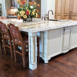 Custom kitchen island with granite countertops and white custom cabinetry
