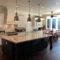 Black kitchen island with light granite countertop and custom cabinetry in Fresno