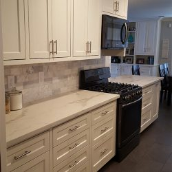 Kitchen renovation with white cabinetry and white granite counter tops