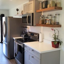 Kitchen remodel with white countertops, grey cabinetry, and stainless steel appliances