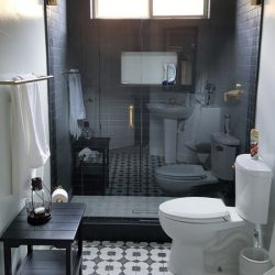 Bathroom with tiled patterned floor and dark brown tiled shower