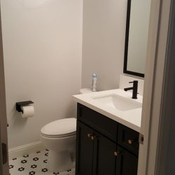 White bathroom with tiled patterned floor and dark brown vanity