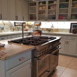 Custom kitchen design with white cabinetry and stainless steel appliances in Clovis