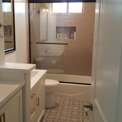 White bathroom with tiled shower and tiled patterned floor