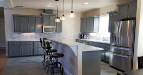Kitchen with sitting area and dark grey cabinetry