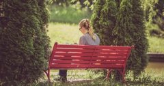 Image of a woman sitting on a red bench and reading a book.