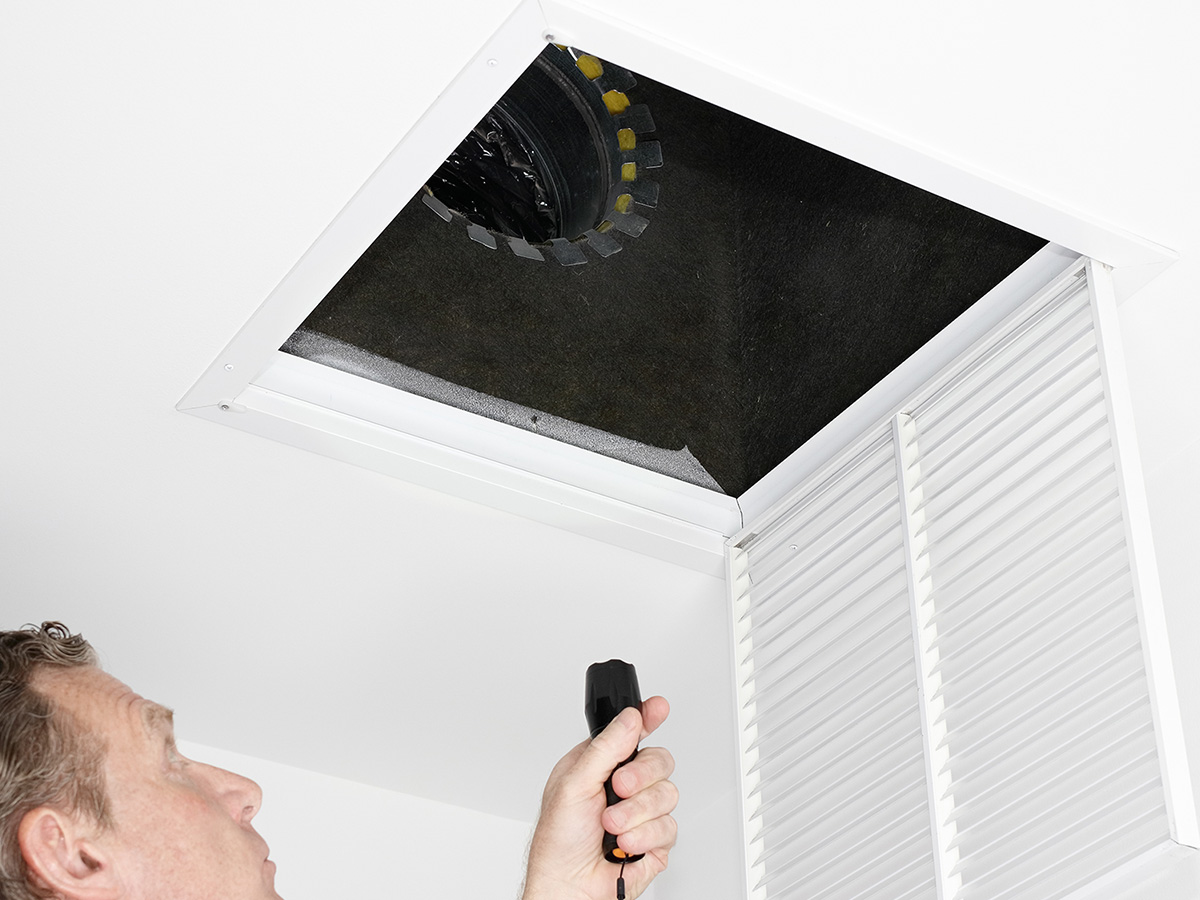 Man looks inside of air duct with a flashlight.
