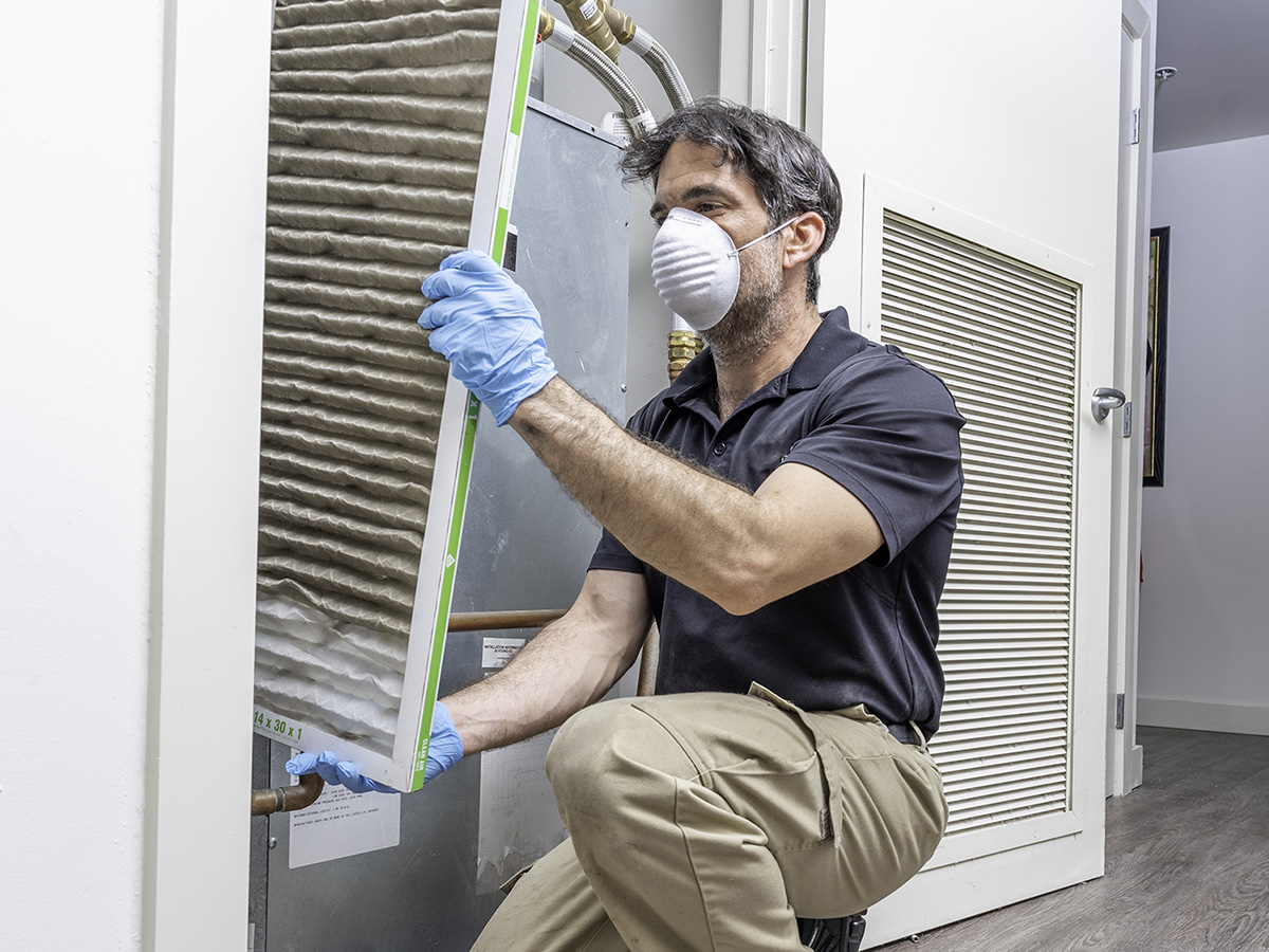 Man changes large air filter from air duct system in a building.