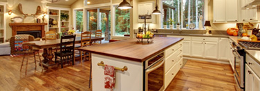 Wide image of a kitchen with wood floors and other features