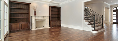 Wide image of an empty room with hardwood flooring