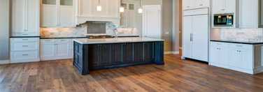 Wide image of a kitchen island with hardwood flooring