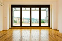 Image of a refinished hardwood floor among massive windows